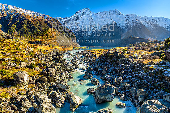 Mt Sefton (3151m)  and Footstool (2764m right) above the Mueller Glacier lake and valley, with Hooker River rushing past. Southern Alps, Main Divide. Sealy Range at left, Aoraki / Mount Cook National Park, MacKenzie District, Canterbury Region, New Zealand (NZ) stock photo.