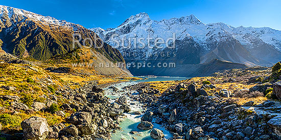 Mt Sefton (3151m)  and Footstool (2764m right) above the Mueller Glacier lake and valley, with Hooker River rushing past. Southern Alps, Main Divide. Sealy Range at left. Panorama, Aoraki / Mount Cook National Park, MacKenzie District, Canterbury Region, New Zealand (NZ) stock photo.