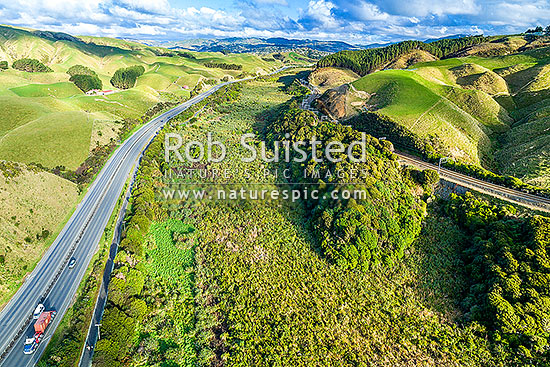 Taupo Swamp, a protected wetland under the QEII National Trust. Taupo Stream, hemmed in by the NIMT railway line and State Highway 1 (SH1). Aerial view looking south to Porirua, Plimmerton, Porirua City District, Wellington Region, New Zealand (NZ) stock photo.