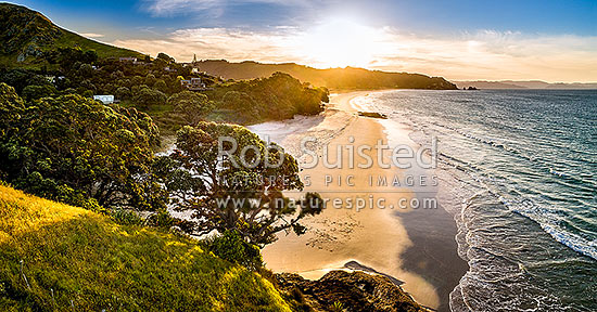 Otama beach sunset, looking towards Motuhua Point, with homes and baches above at sunset. Panorama, Otama Beach, Coromandel Peninsula, Thames-Coromandel District, Waikato Region, New Zealand (NZ) stock photo.