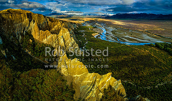Omarama Clay Cliffs eroding above the Ahuriri River, an evening aerial view looking towards Omarama, Omarama, Waitaki District, Canterbury Region, New Zealand (NZ) stock photo.