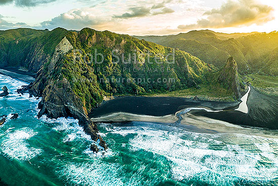 Karekare Beach and Union Bay at dawn. Farley Point left, The Watchman and Karekare Stream right. Waitakere Ranges behind. Aerial view, Karekare Beach, Waitakere City District, Auckland Region, New Zealand (NZ) stock photo.