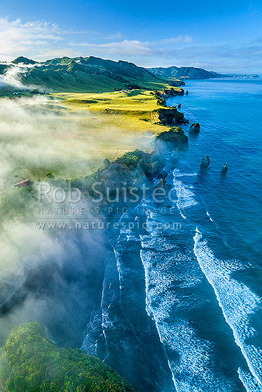 Tongaporutu Coastline on a moody misty morning. Looking south past Three Sisters rocks towards Pariokariwa Pt and Whitecliffs. Aerial view, North Taranaki, Tongaporutu, New Plymouth District, Taranaki Region, New Zealand (NZ) stock photo.