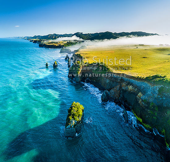 Tongaporutu River mouth on the North Taranaki coast, as morning inversion cloud flows down river valley. Aerial view looking north past the Three Sisters rocks.  Aerial view, square format, Tongaporutu, New Plymouth District, Taranaki Region, New Zealand (NZ) stock photo.