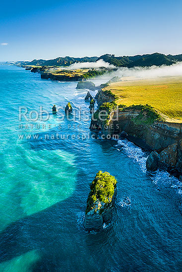 Tongaporutu River mouth on the North Taranaki coast, as morning inversion cloud flows down river valley. Aerial view looking north past the Three Sisters rocks.  Aerial view, Tongaporutu, New Plymouth District, Taranaki Region, New Zealand (NZ) stock photo.
