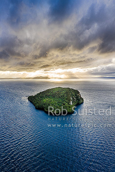 Motutaiko Island in southern Lake Taupo (Taupomoana) on a moody evening. Crepuscular rays on the western lake shores behind. Aerial view, Motutere, Taupo District, Waikato Region, New Zealand (NZ) stock photo.