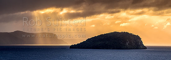 Lake Taupo with moody weather breaking. Motutaiko Island in Lake Taupo (Taupomoana). Crepuscular rays on the western lake shore cliffs of Karangahape behind. Panorama, Motutere, Taupo District, Waikato Region, New Zealand (NZ) stock photo.