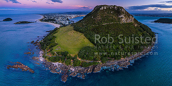 Mount Maunganui, or Mauao, at the Tauranga Harbour Entrance. 231m high lava dome. Moturiki and Motuotau Islands at left. Aerial panorama at dusk, Mount Maunganui, Tauranga District, Bay of Plenty Region, New Zealand (NZ) stock photo.