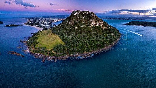 Mount Maunganui, or Mauao, at the Tauranga Harbour Entrance. 231m high lava dome. Moturiki and Motuotau Islands at left. Aerial view at dusk, Mount Maunganui, Tauranga District, Bay of Plenty Region, New Zealand (NZ) stock photo.