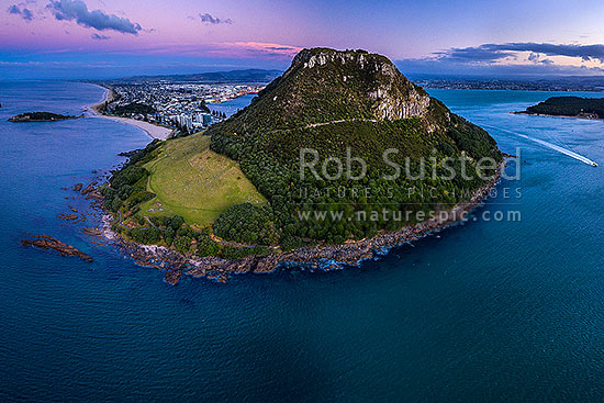 Mount Maunganui, or Mauao, at the Tauranga Harbour Entrance. 231m high lava dome. Moturiki Island at left, Tauranga City right. Aerial view at dusk, Mount Maunganui, Tauranga District, Bay of Plenty Region, New Zealand (NZ) stock photo.