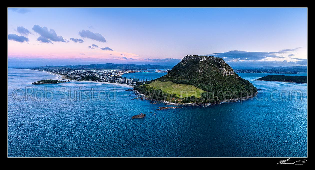 Image of Mount Maunganui, or Mauao, at the Tauranga Harbour Entrance. 231m high lava dome. Moturiki Island at left, Tauranga Port cenre, City right. Aerial view at dusk, Mount Maunganui, Tauranga District, Bay of Plenty Region, New Zealand (NZ) stock photo image