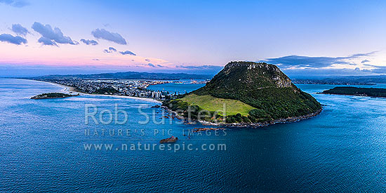 Mount Maunganui, or Mauao, at the Tauranga Harbour Entrance. 231m high lava dome. Moturiki Island at left, Tauranga Port cenre, City right. Aerial view at dusk, Mount Maunganui, Tauranga District, Bay of Plenty Region, New Zealand (NZ) stock photo.