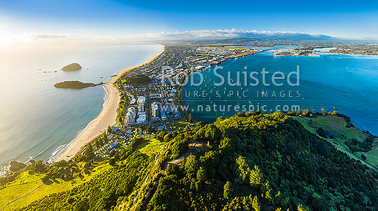 Mount Maunganui, or Mauao summit above Mt Maunganui Beach, at Tauranga Harbour Entrance. 231m high lava dome. Moturiki and Motuotau Islands at left. Tauranga Port and City at right. Aerial view, Mount Maunganui, Tauranga District, Bay of Plenty Region, New Zealand (NZ) stock photo.