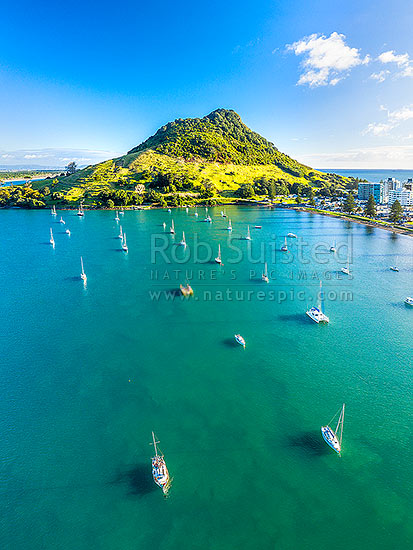 Mt Maunganui Mauao (231m lava dome) above Tauranga Harbour and moored yachts. Mt Maunganui Beach right. Aerial view, Mount Maunganui, Tauranga District, Bay of Plenty Region, New Zealand (NZ) stock photo.