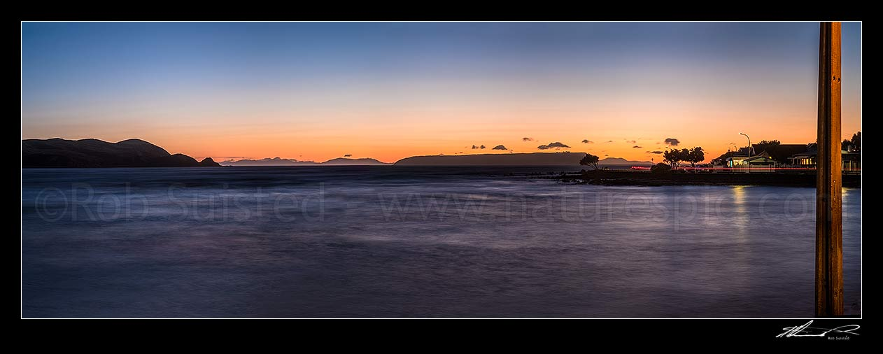 Image of Plimmerton Beach sunset. Titahi Bay coast at left, Mana Island centre right, and South Island in distance. Panorama, Plimmerton, Porirua City District, Wellington Region, New Zealand (NZ) stock photo image