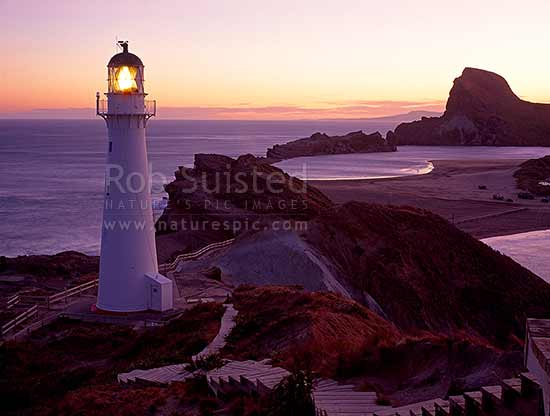 Castlepoint Lighthouse at dusk, looking across lagoon towards Castle rock, Castlepoint, Masterton District, Wellington Region, New Zealand (NZ) stock photo.